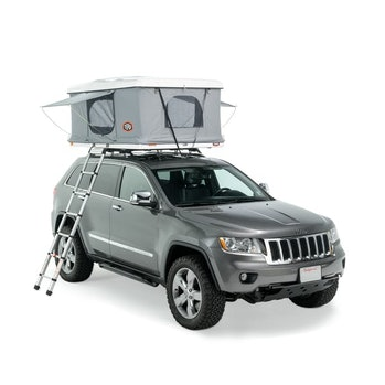 A silver Jeep with a canopy/storage unit on top.