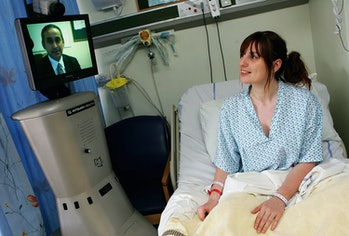 A member of the St Mary's Hospital medical staff operates the Sister Mary RP6 (Remote Presence Robot), as he communicates with a patient via a remote console system in London, England.