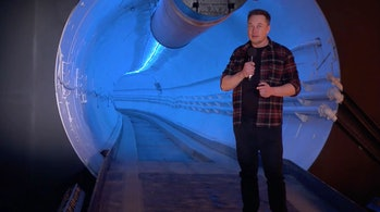 "Musk standing next to his ""wormhole"" tunnel."