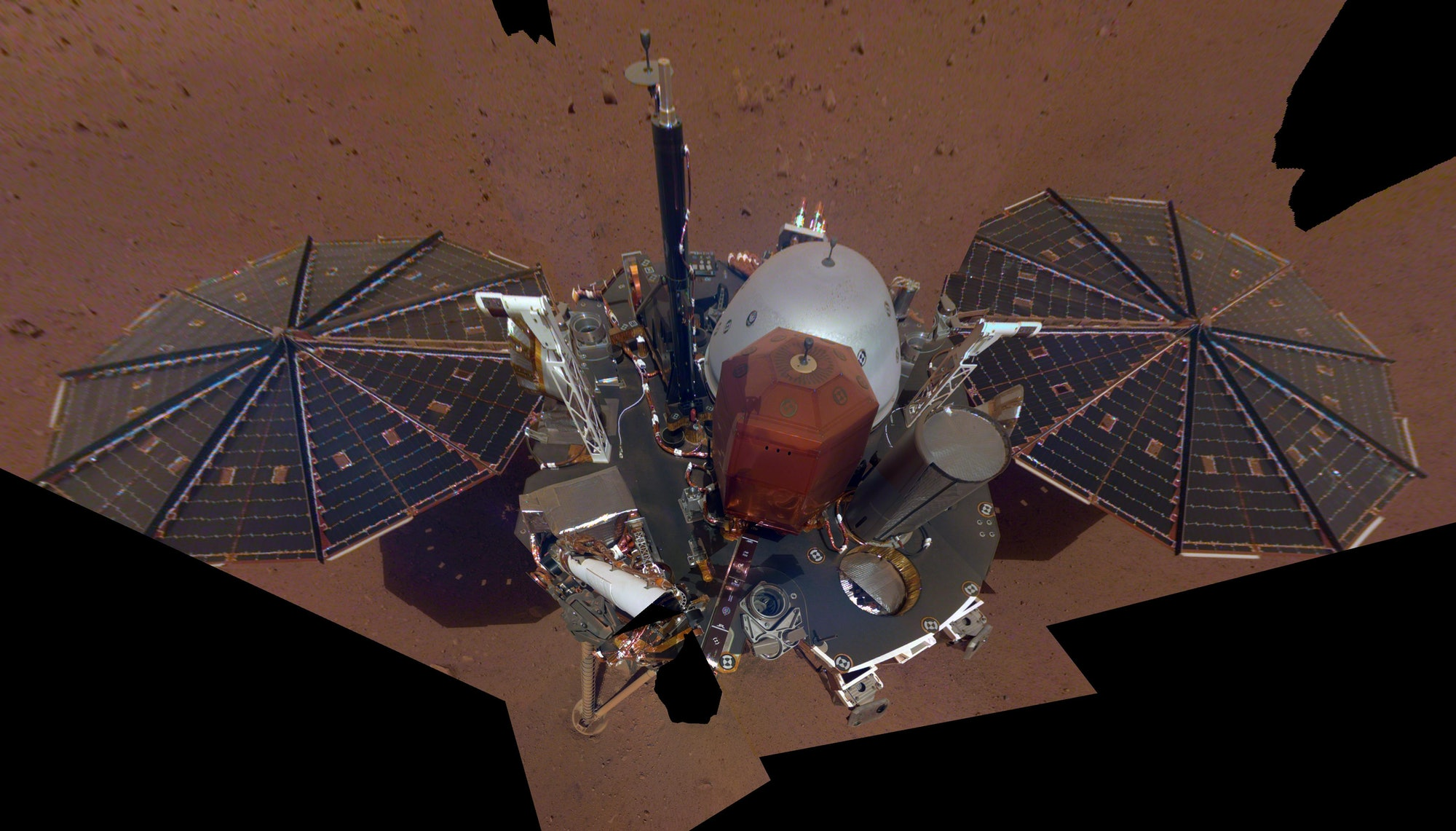 This is NASA InSight's first full selfie on Mars. It displays the lander's solar panels and deck. On top of the deck are its science instruments, weather sensor booms and UHF antenna. The selfie was taken on Dec. 6