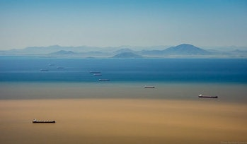 A photo depicting two threats to the Great Barrier Reef: coal ships anchored near Abbot Point and a flood plume from the Burdekin River (February 2019); such plumes can carry pollutants and debris to the Great Barrier Reef.
