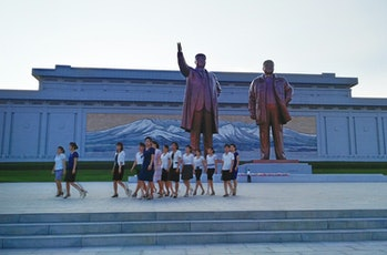 PYONGYANG, NORTH KOREA - AUGUST 23: North Koreans visit the Mansudae Grand Monument on August 23,2015in Pyongyang, North Korea. North and South Korea today came to an agreement to ease tensions following an exchange of artillery fire at the demilitarized border last week. (Photo by Xiaolu Chu/Getty Images)