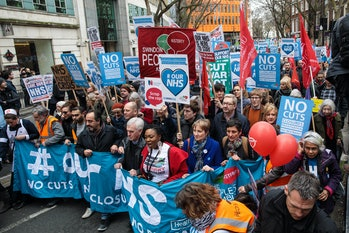LONDON, ENGLAND - MARCH 04: Protesters carry banners and placards through central London during a de...