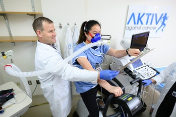 This picture shows Memorial Sloan Kettering Exercise Physiologist Dan Townend conducts a cardiopulmonary exercise test to assess cardiorespiratory fitness on Catherine Lee.