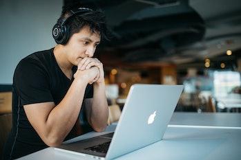 Man macbook headphones listening computer