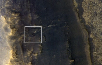 NASA's Opportunity rover appears as a small blip in this image of the dusty Martian surface.