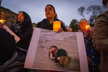 woman hold's photo of Aylan Kurdi at a vigil