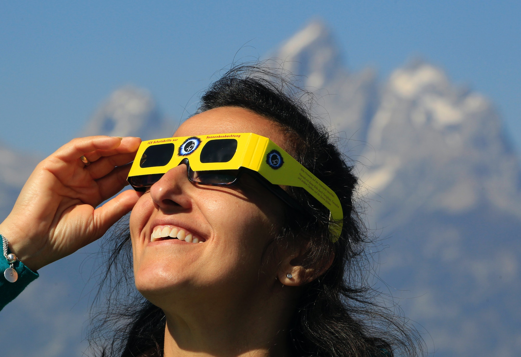 JACKSON, WY - AUGUST 21: A woman views the solar eclipse in the first phase of a total eclipse in Grand Teton National Park on August 21, 2017 outside Jackson, Wyoming. Thousands of people have flocked to the Jackson and Teton National Park area for the 2017 solar eclipse which will be one of the areas that will experience a 100% eclipse on Monday August 21, 2017. (Photo by George Frey/Getty Images)