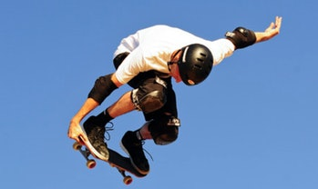 Tony Hawk flies on a sea blue sky.