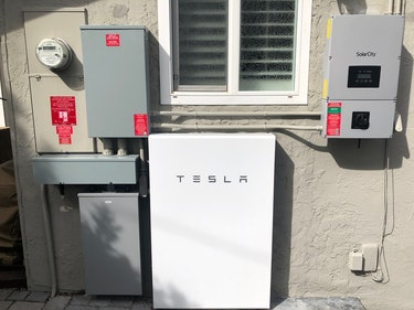 Amanda Tobler's Powerwall, paired with a Tesla Solar Roof, on the outside of the property.