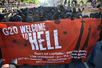 HAMBURG, GERMANY - JULY 06: Protesters dressed in all black hold up a banner as they take part in th...