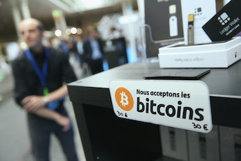 HANOVER, GERMANY - MARCH 16: A sign in French that reads: 'We acceptbitcoins' hangsata display of the LedgerWallet Nano USB stick that enables security-protected transactions with bitcoins at the 2015 CeBIT technology trade fair on March 16,2015in Hanover, Germany. China is this year's CeBIT partner. CeBIT is the world's largest tech fair and will be open from March 16 through March 20. (Photo by Sean Gallup/Getty Images)
