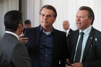 Brazilian President Jair Bolsonaro talks to two other men