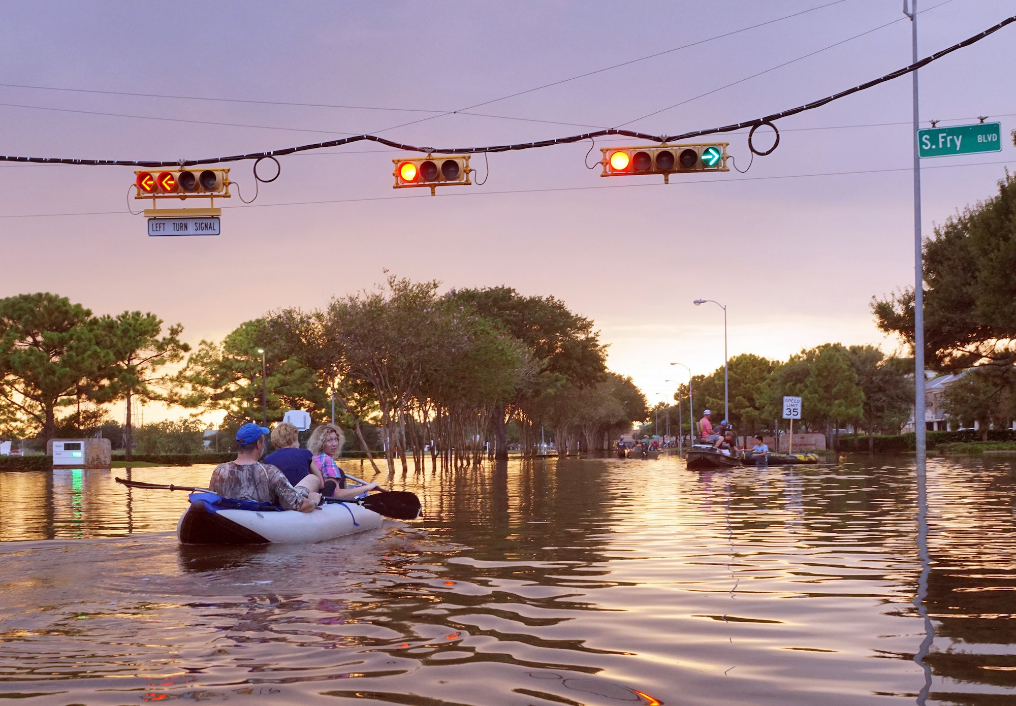 working traffic lights over flooded Houston streets and boats with people at sunset