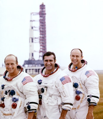 From left to right: Pete Conrad, Dick Gordon, and Alan Bean pose with their Apollo 12 Saturn V moon rocket in the background on the pad at Cape Canaveral on 29 October 1969
