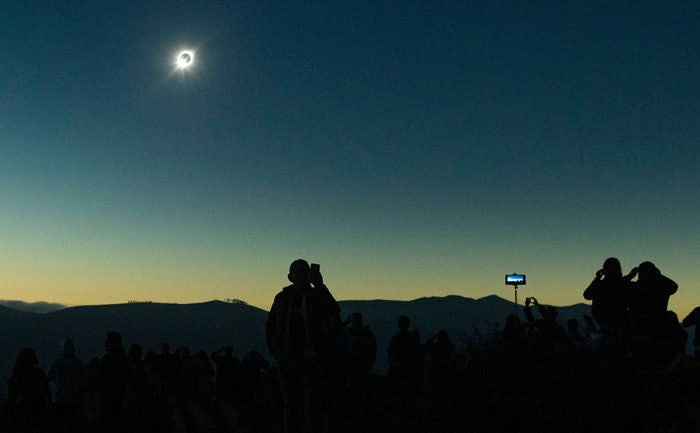 Thousands of tourists and locals gathered to watch at La Higuera, Chile.CREDIT:Esteban Felix/AP/Shutterstock