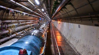 View of the LHC in its tunnel at CERN. The LHC is a 27-kilometer-long underground ring of superconducting magnets housed in this pipe-like structure, or cryostat. The cryostat is cooled by liquid helium to keep it at an operating temperature just above absolute zero. It will accelerate two counterrotating beam of protons to an energy of 7 tera-electron volts (TeV) and then bring them to collide head-on. Several detectors are being built around the LHC to detect the various particles produced by the collision.