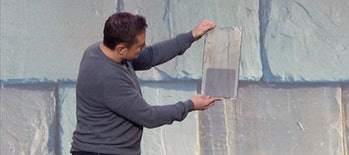 Elon Musk holding a slate solar tile.