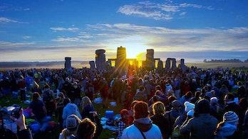 Revelers watch the Solstice Sun rise over Stonehenge Heel Stone