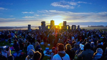 Revelers watch the Solstice Sun rise over Stonehenge Heel Stone