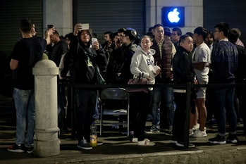 Customers take pictures with their mobile phones as they queue at Puerta del Sol Apple Store before ...