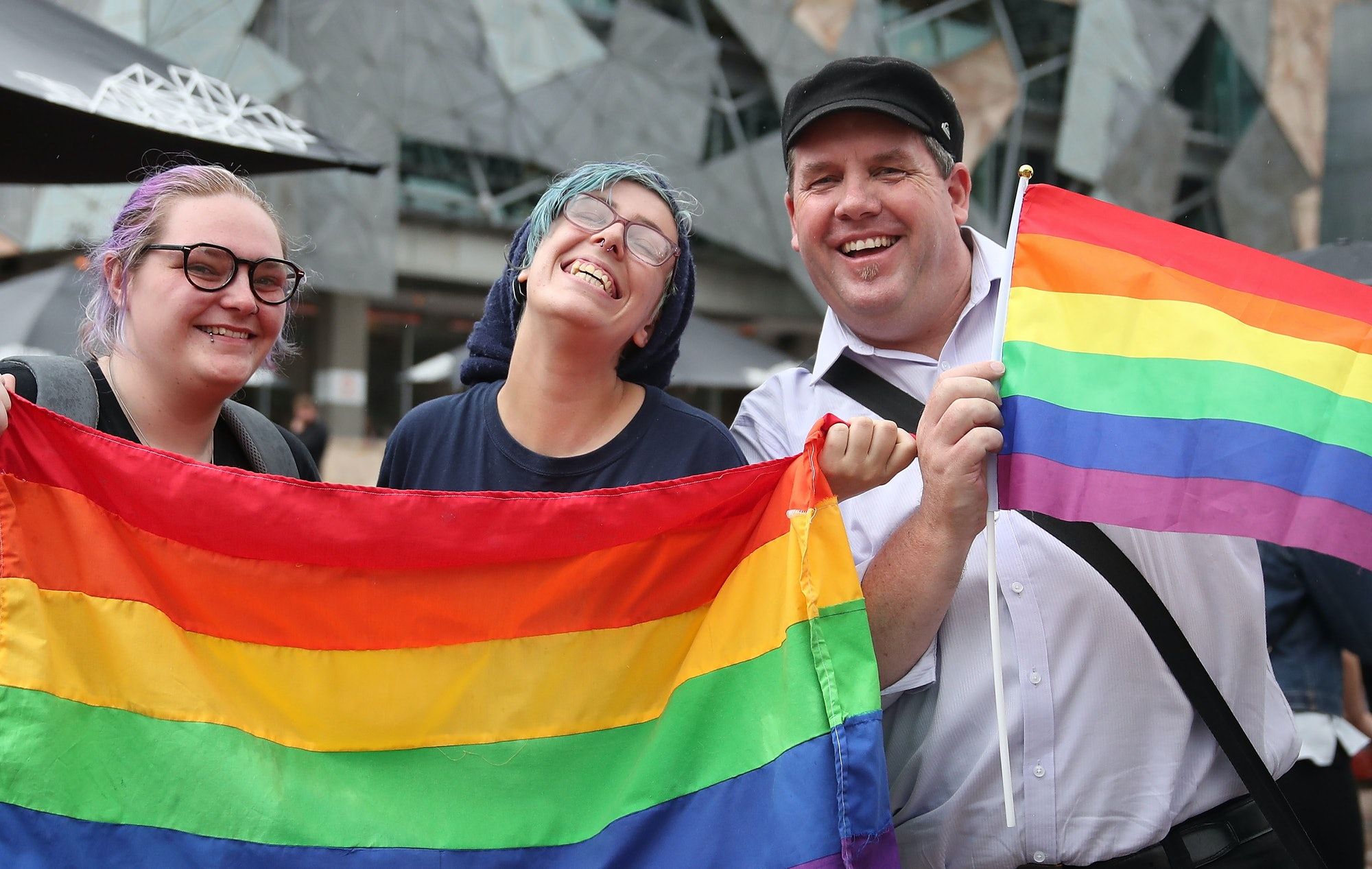 People celebrate as a crowd gathers to watch a large television screen at Federation Square as it is announced that same-sex marriage will be legal in Australia