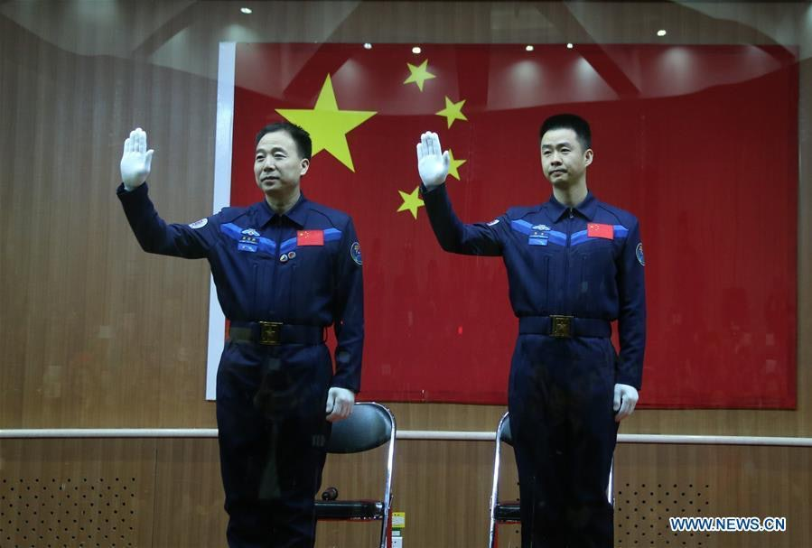 Jing Haipeng and Chen Dong wave to bystanders before boarding the Shenzou-11.