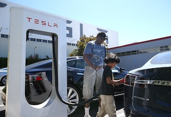 FREMONT, CA - AUGUST 16: Jinyao Desandies (R) and Dandre Desandies (L) plug the Tesla Supercharger into their Tesla Model S sedan outside of the Tesla Factory on August 16, 2013 in Fremont, California. Tesla Motors opened a new Supercharger station with four stalls for public use at their factory in Fremont, California. The Superchargers allow owners of the Tesla Model S to charge their vehicles in 20 to 30 minutes for free. There are now 18 charging stations in the U.S. with plans to open more in the near future. (Photo by Justin Sullivan/Getty Images)