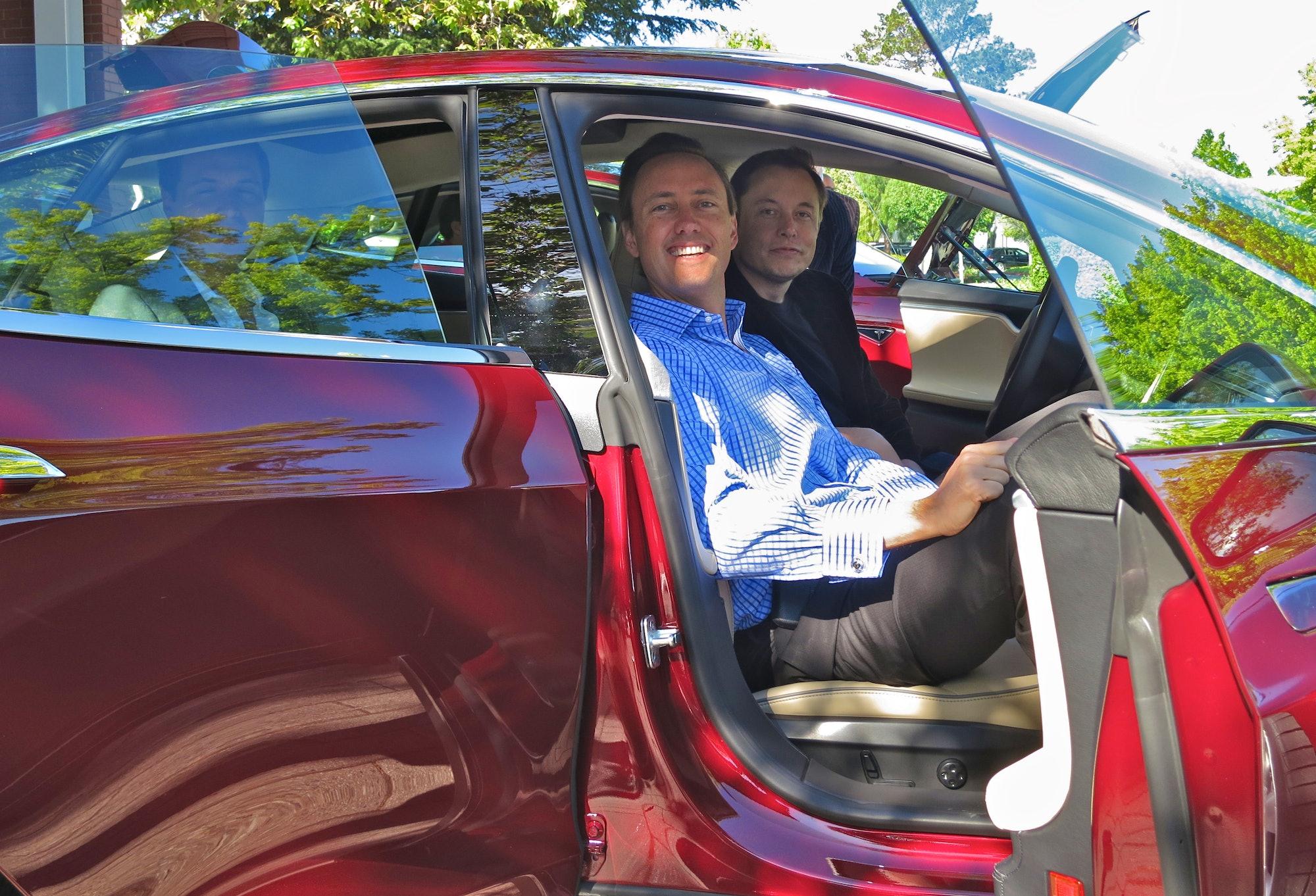 Kimbal and Elon Musk in a Tesla.