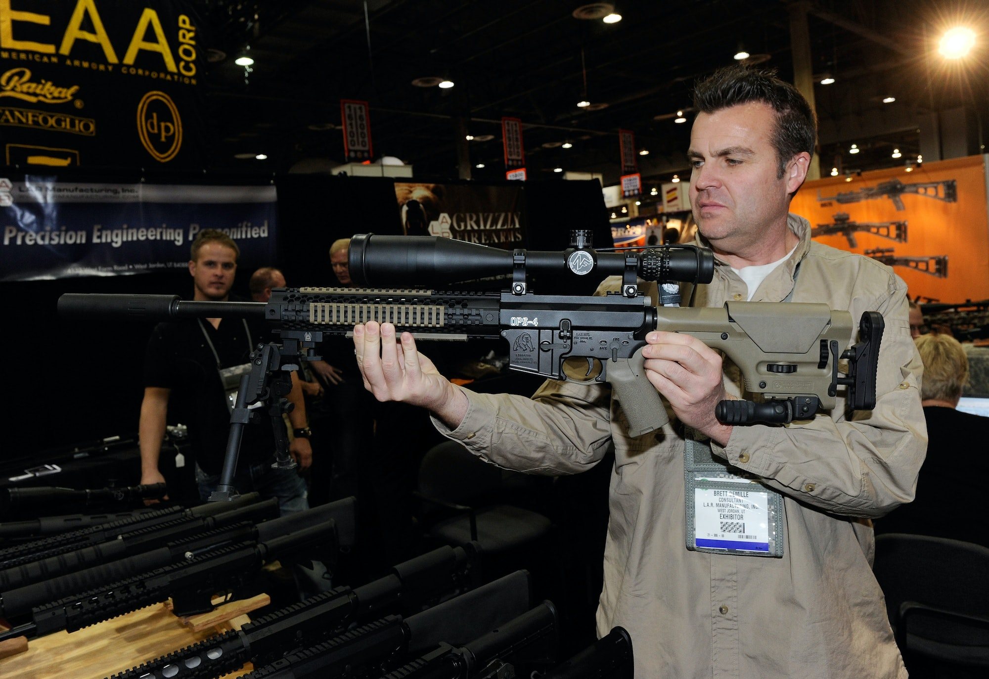 LAS VEGAS, NV - JANUARY 18: Brett DeMille demonstrates an AR-15 rifle with a silencer at the L.A.R./Grizzly Firearms booth at the National Shooting Sports Foundation's 33rd annual Shooting, Hunting and Outdoor Trade (SHOT) Show at the Sands Expo and Convention Center January 18, 2011 in Las Vegas, Nevada. The shooting rampage in Tucson, Arizona on January 8 that killed six people and injured 13 people, including U.S. Rep. Gabrielle Giffords (D-AZ), has sparked debate about gun laws in the media and Congress. (Photo by Ethan Miller/Getty Images)