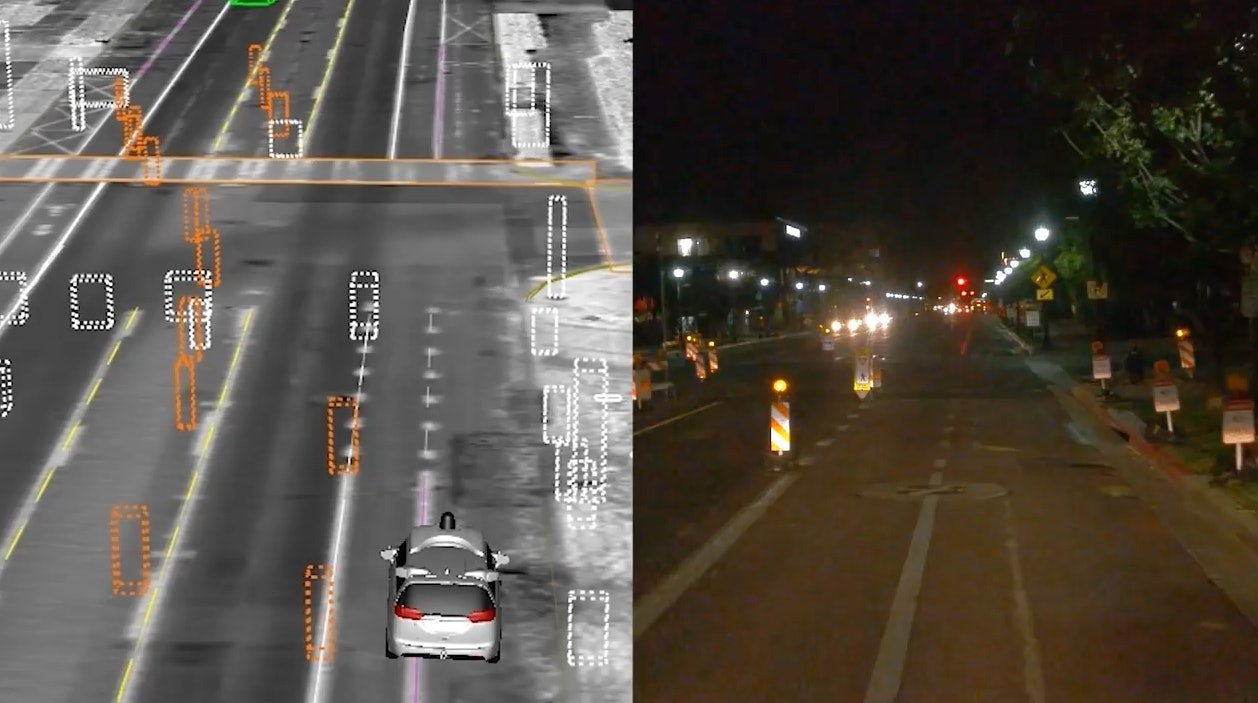 Waymo driving through construction lanes at night.