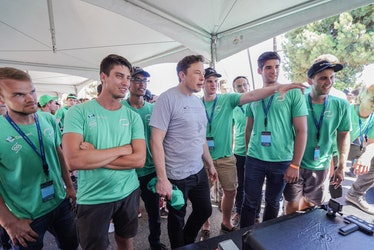Musk standing with the Delft team.