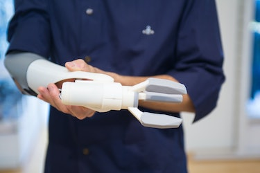 A potential user tenses his muscles to open the pinch mechanism on this 3D printed prosthetic arm in Okayama, Japan.