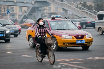 Woman with protective mask rides bike on a busy street in Dongcheng District in Beijing
