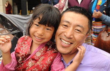 Tibetan girl in a red & gold silk chuba / pink blouse, her daddy in a purple cotton shirt, woman hol...