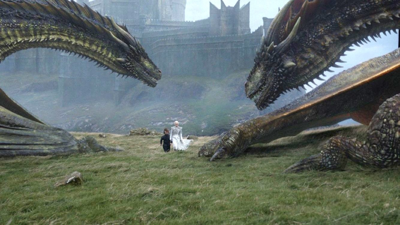 On Dragonstone, Tyrion and Daenerys walk nearRhaegal and Viserion.