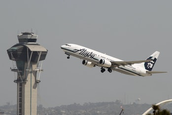 An Alaska Airlines jet passes the air traffic control tower at Los Angles International Airport (LAX).