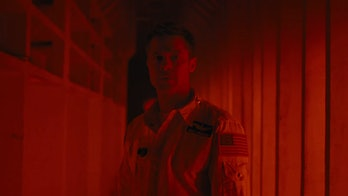 Brad Pitt as Roy McBride in a red hallway in 'Ad Astra'