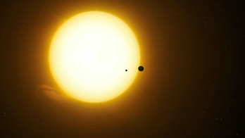 This artist's rendering shows what it may look like for the planet Kepler-1625b and its moon to pass across the star Kepler-1625.
