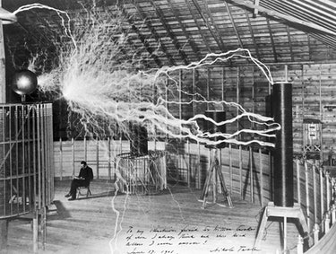 Nikola Tesla sits calmly next to a massive Tesla coil -- or does he? -- in a photo that earned him n...