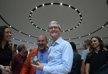 Apple CEO Tim Cook (R) and Apple chief design officer Jonathan Ive (L) look at the new Apple iPhone ...