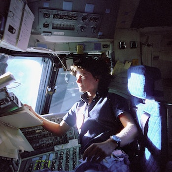 (June 1983) Astronaut Sally K. Ride, mission specialist on STS-7, monitors control panels from the pilot's chair on the Flight Deck. Floating in front of her is a flight procedures notebook. Image Number: S83-35783 Date: June 18-24, 1983