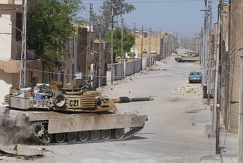 NAJAF, IRAQ - AUGUST 17: American Army Abrams M1 tanks from the 1st Cavalry Division 2nd Battalion 7th Cavalry roll through the streets during fighting with Shiite militia August 17, 2004 in Najaf, Iraq. Iraqi political and religious leaders, trying to end a radical Shi'ite uprising, flew into Najaf to try and quell the violence. (Photo by Joe Raedle/Getty Images)