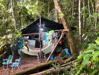 a tent in the woods surrounded by clothes on clotheslines