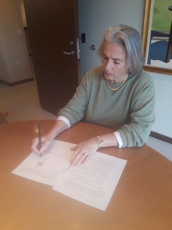 Purcell signing the blockchain-enabled deed.