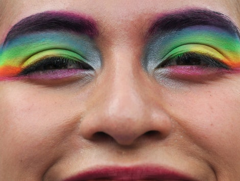 A person with rainbow flags painted on their eyelids. Queer meaning is very personal.