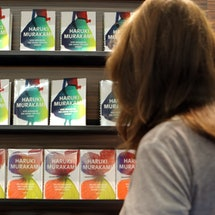 A woman looks at books for sale by Haruki Murakami.