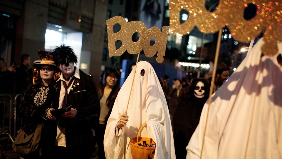 A crowd of trick-or-treaters outside on Halloween night