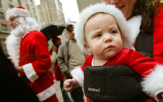 a baby wearing a santa suit in a baby bjorn