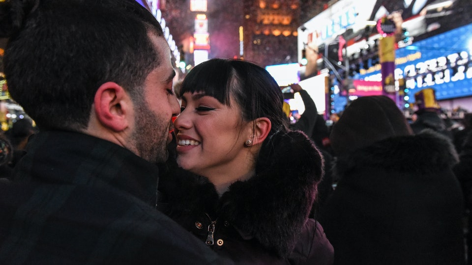 couple about to kiss at midnight on new year's eve